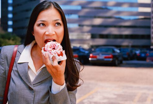 A woman eats a donut on the way to work.