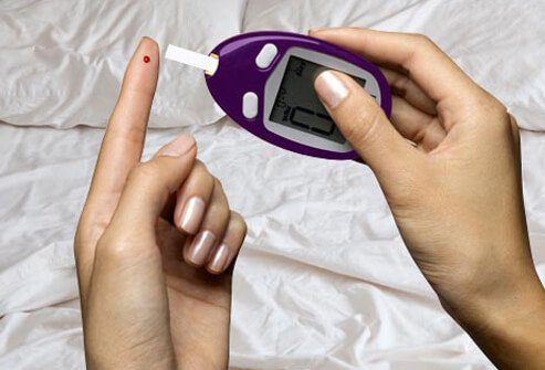A woman checking her blood sugar level before bedtime.