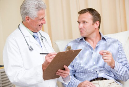 A man describes his abdominal pain symptoms with his doctor.