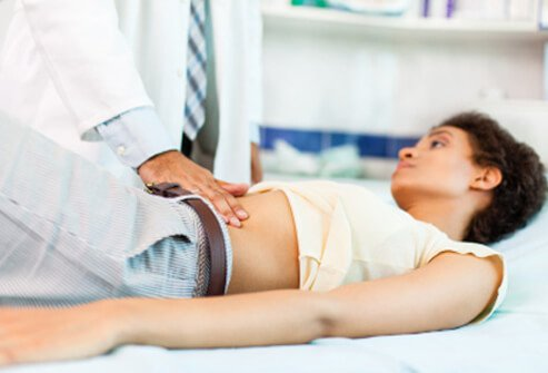 A doctor examines a woman with abdominal pain.