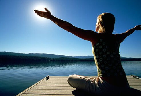 A woman sitting on a dock by a lake, getting vitamin D.