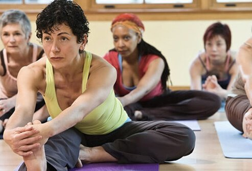 A group of older women doing yoga.