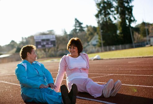 Two women sitting on a running track.