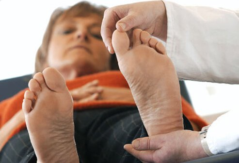 A woman at the doctor getting her feet examined.