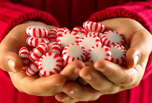 A photo of hands with peppermints.