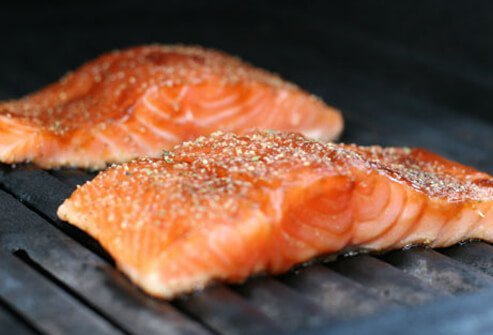 Salmon steaks cook on a grill.