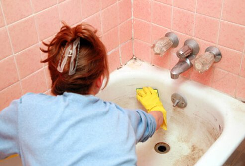 A woman cleans mold and mildew from a bathroom tub.