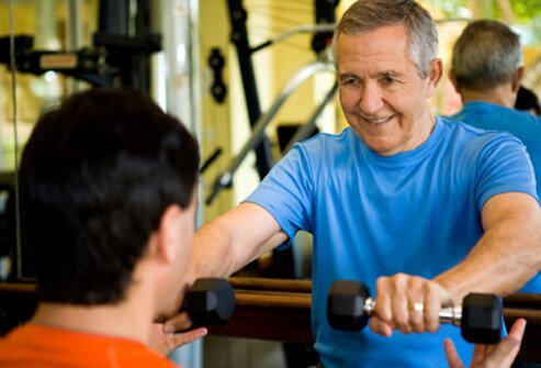 A senior man weight training with a personal trainer.