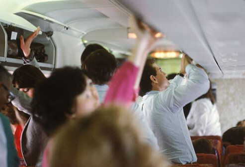 Photo of passengers on airplane stowing their luggage.