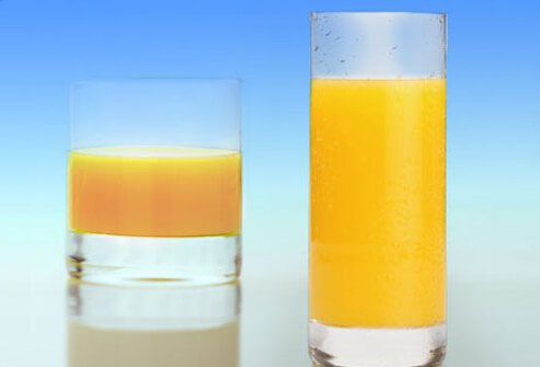 Big and small glasses of orange juice.