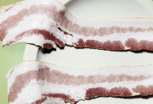 Uncooked bacon on a plate.
