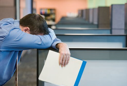 A man with shift work sleep disorder resting his head on an office cubicle.