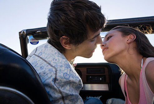 Photo of couple kissing in car, still at risk for STDs.