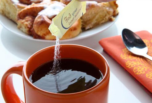 Photo of pouring sweetener into coffee.