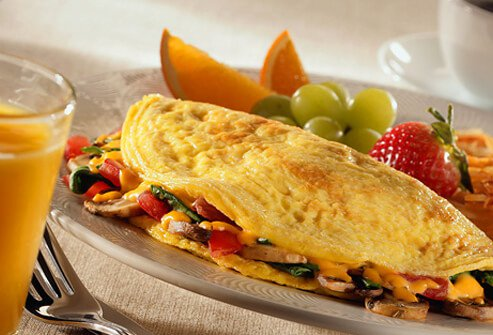 Tomato and cheese veggie omelet served with fruit and orange juice.