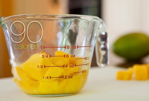 A measuring cup filled with frozen mango cubes.