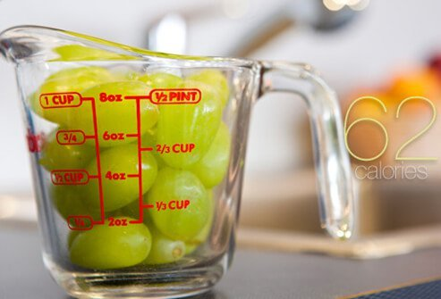 A measuring cup full of grapes.