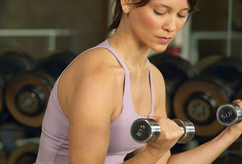 Woman lifting light weights in the gym.