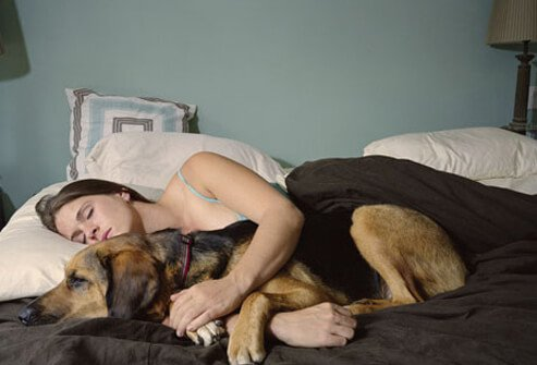 Photo of a woman sleeping with her dog.