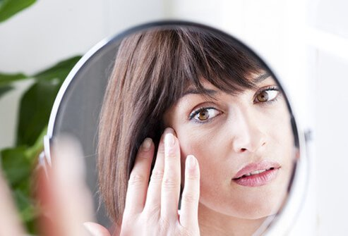 A woman examines her skin in the mirror.