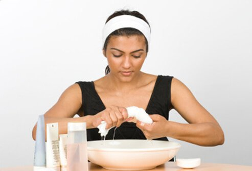 A woman prepares to wash her face.