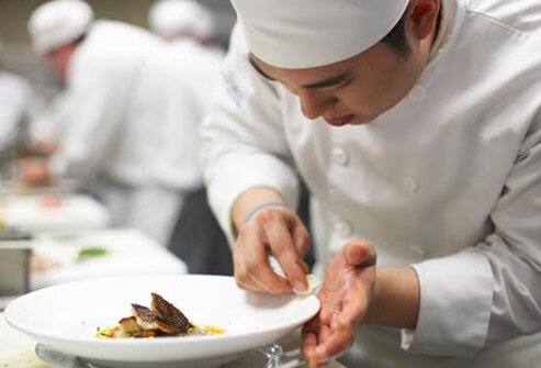 Photo of chef wiping plate.