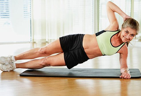 A trainer showing proper alignment for a side plank.