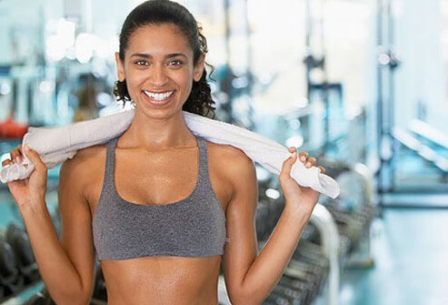 A young woman holding a towel in the gym.