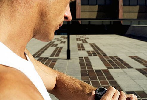 A man looking at his watch before a workout