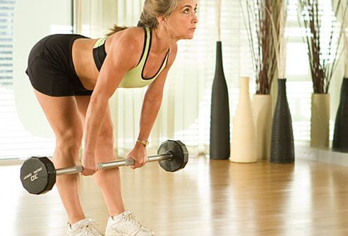 A trainer using a barbell for hamstring exercises.