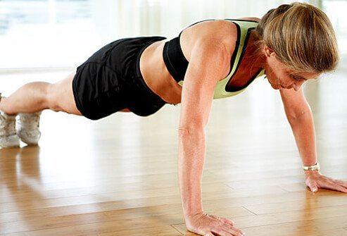 A trainer doing push-ups, arms extended.