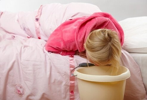 A sick girl keeps a trash can next to her bed in case she vomits.