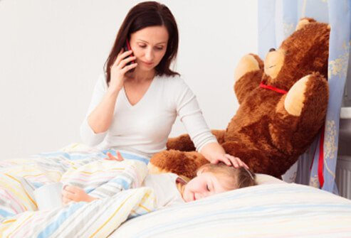 A mother talks on the phone concerned about her child's pain.