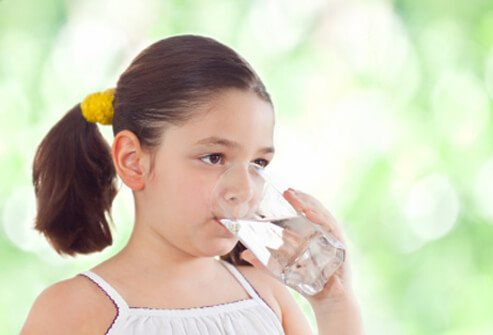 A young girl drinking a glass of water.