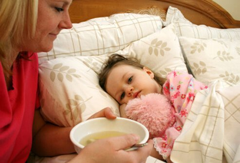 A mother feeding her daughter a bowl of soup in bed.