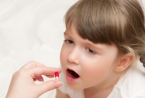 A girl is given an antibiotic pill by hand.