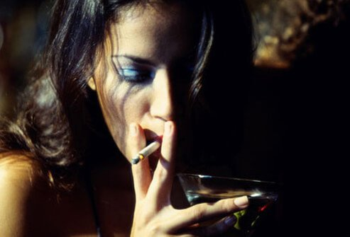 Photo of a woman smoking a cigarette with a martini.