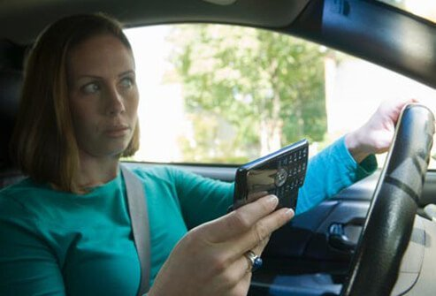 Photo of a woman texting while driving.