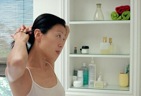 A woman ties her hair back from her face.