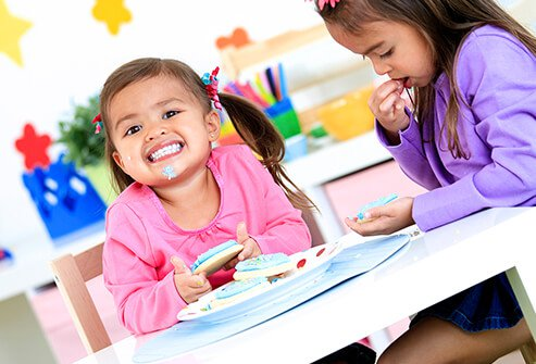An elementary school student and her friend enjoying cookies.