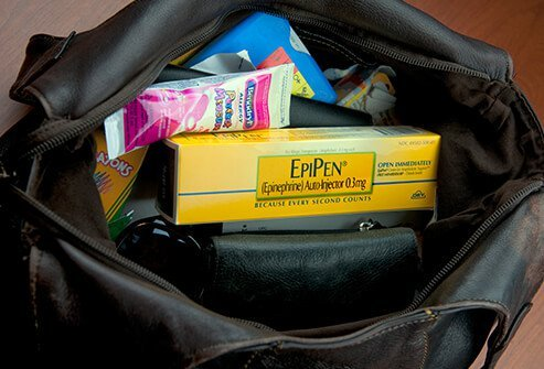 A close up of a purse with allergy medication inside.