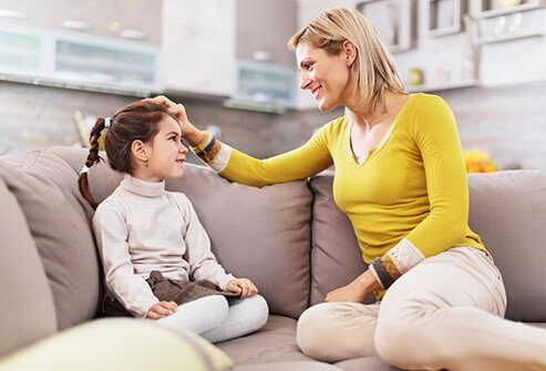 A mother and daughter having a conversation on the couch.
