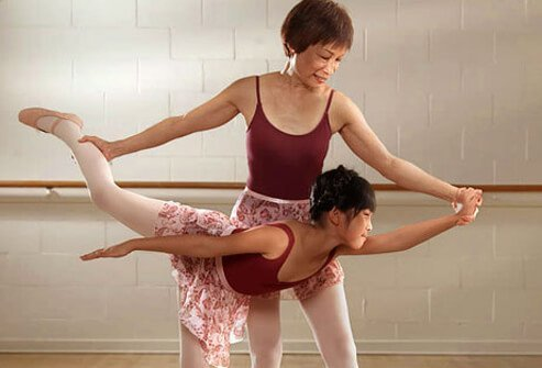 Photo of an arthritic woman with her grandchild doing ballet.
