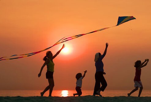 Photo of a woman getting active outdoors flying kite with kids.