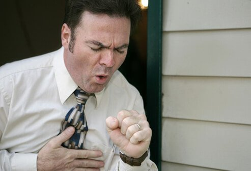 A man shows symptoms of wheezing, coughing, and chest tightness, signifying an asthma attack.