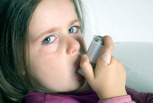 A young girl uses an inhaler to treat her asthma.