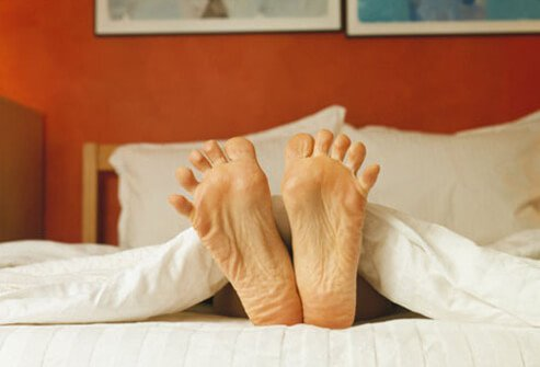 Bare feet in bed.