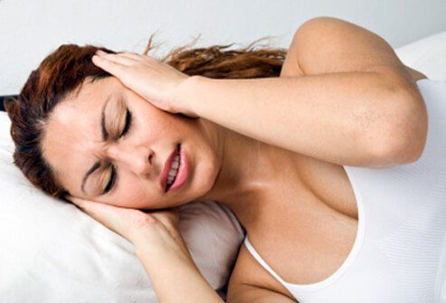 A woman suffers from benign paroxysmal positional vertigo (BPPV) as she rolls over in bed.