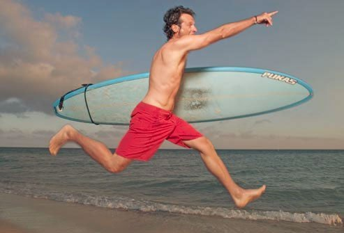 Man running with surfboard