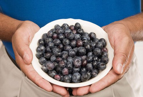 Photo of a man holding a bowl of blueberries.